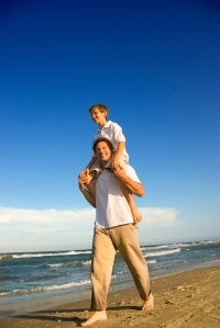 Dad carrying son on his shoulders.